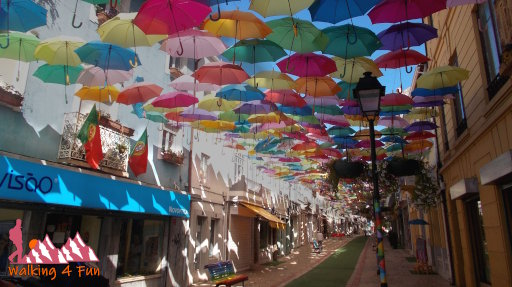 Hundreds of colorful umbrellas provide shade along this pedestrian street in Portugal